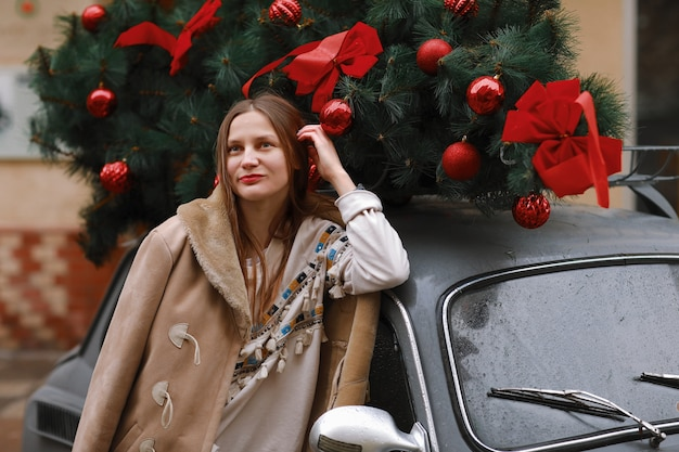 Meisje op een de wintergang in de stad, sneeuw, buiten. winter straat in de stad. gelukkig meisje loopt in de stad op eerste kerstdag.