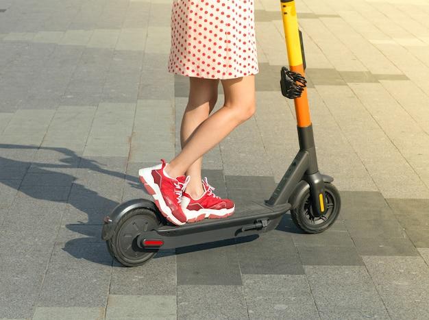 Meisje op een elektrische scooter op een heldere zomerdag in de stad. verhuur van elektrische scooters en buitenactiviteiten in de stad in de zomer.
