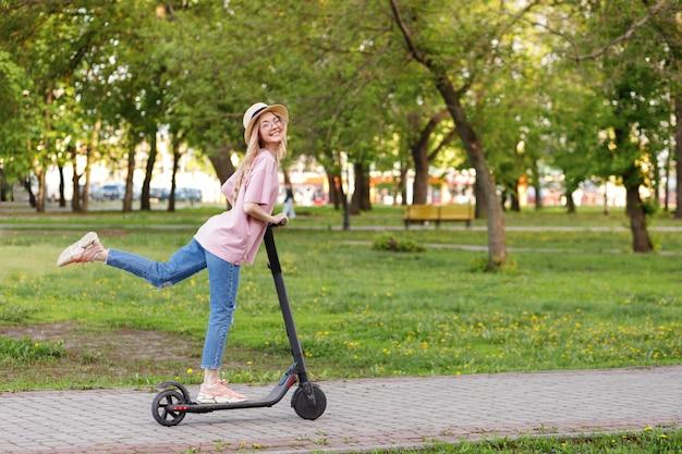 Meisje op een elektronische scooter in een stadspark in de zomer
