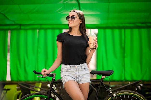 Meisje op een fiets drinken van koffie