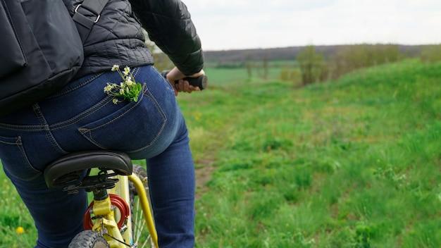 Meisje op een fiets, wilde bloemen in jeanszak, achteraanzicht, foto met kopieerruimte