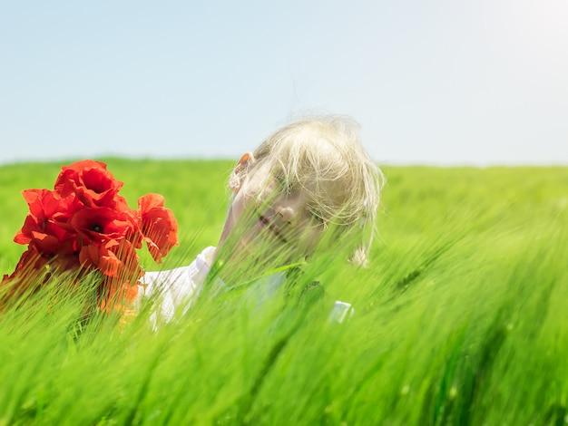 Meisje op een gebied van groene rogge in de wind.