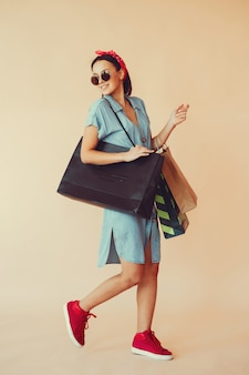 Meisje op een gele muur met boodschappentassen