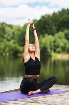 Meisje op een houten brug in de buurt van de rivier die yoga asana's beoefent die de lotuspositie met opgeheven handen uitvoeren