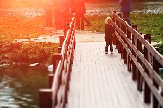 Meisje op een houten brug met haar terug naar de camera in het park bij zonsondergang