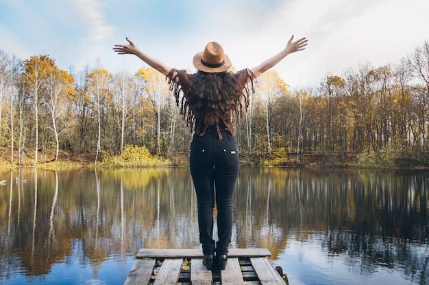 Meisje op een houten oude brug op een meer