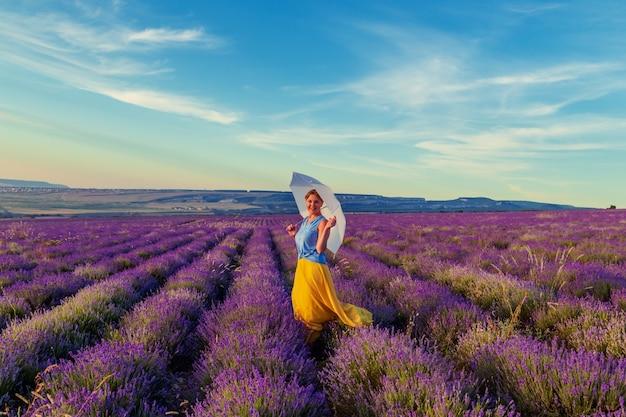 Meisje op een lavendelgebied bij zonsondergang. zonnige zomeravond op de krim.