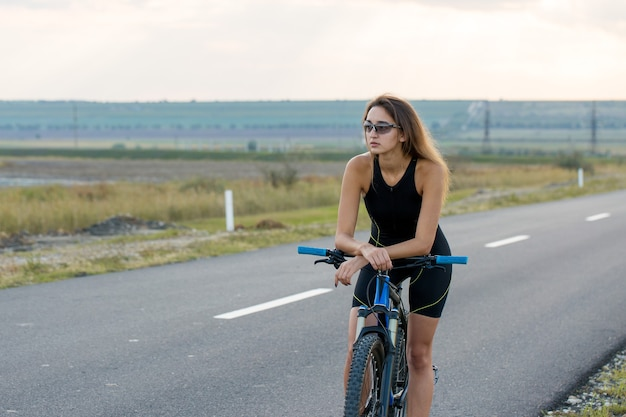 Meisje op een mountainbike op offroad mooi portret van een fietser meisje rijdt op een moderne carbonfiets