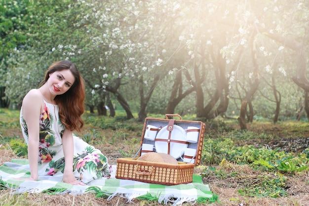 Meisje op een picknick in de appelboomgaard met een mand met producten