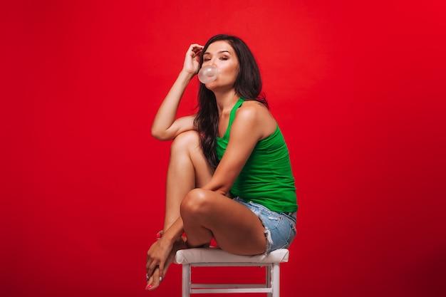 Meisje op een rode achtergrond waait bellen van kauwgom