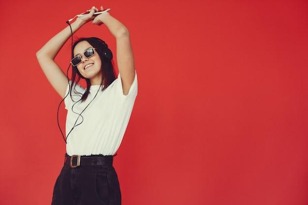 Meisje op een rode muur met een koptelefoon