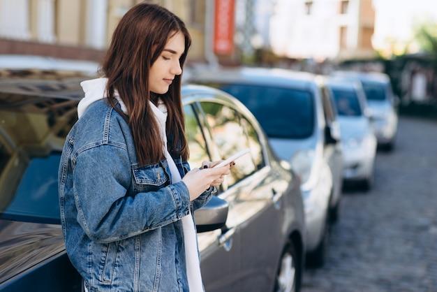 Meisje op een stedelijke achtergrond, kijken naar iets aan de telefoon, leunend op de auto