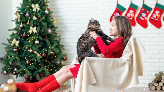 Meisje op een stoel met een kat thuis, kerstboom aan de muur