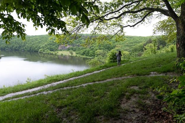Meisje op een wandeling in het bos van de lente bij bewolkt weer.
