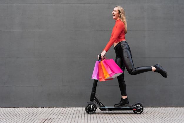 Meisje op elektrische scooter met boodschappentassen