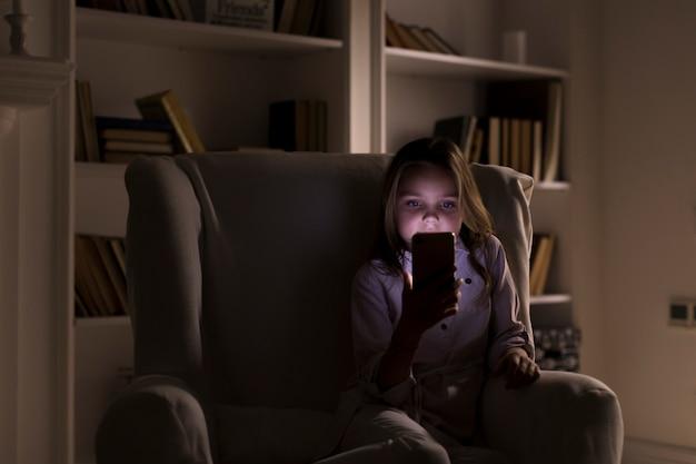 Meisje op haar telefoon binnenshuis spelen
