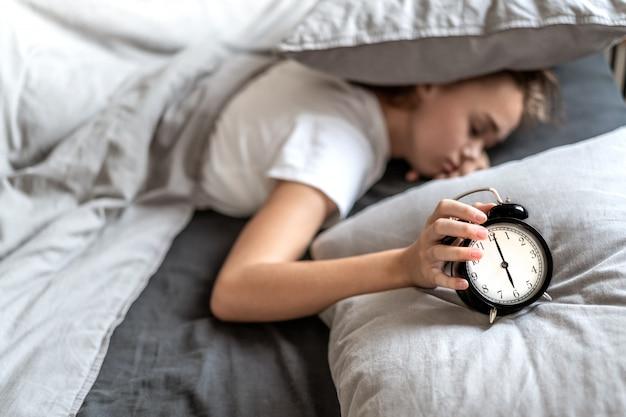 Meisje op het bed dat de wekker uitzet