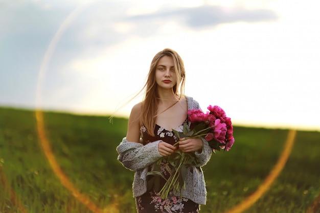 Meisje op het gebied van bloemen. portret van een meisje met roze bloemen