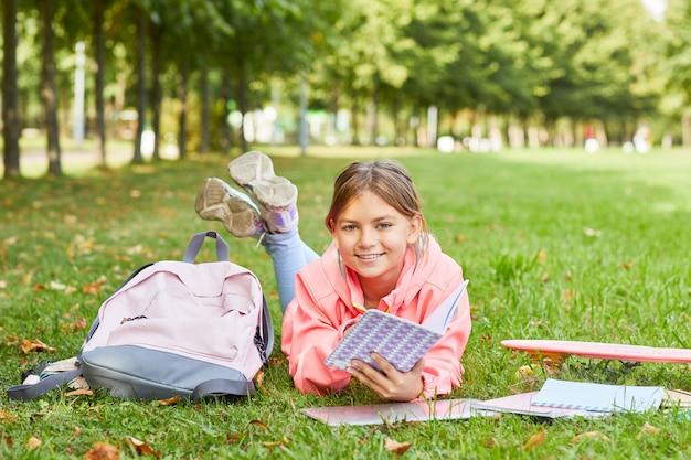 Meisje op het gras met een boek