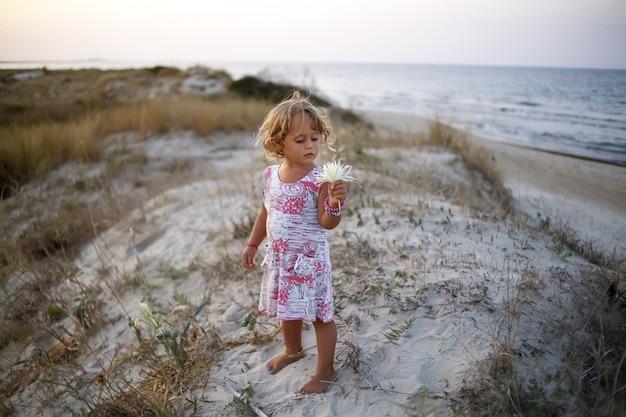 Meisje op het overzees die de bloem bekijken