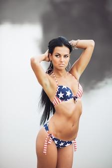 Meisje op het strand met amerikaanse vlag