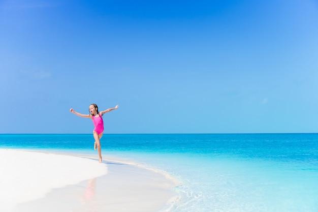 Meisje op het strand met veel plezier in ondiep water op het strand