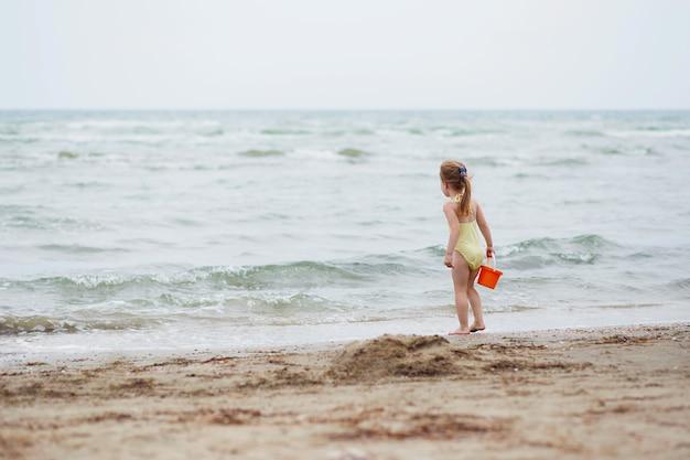 Meisje op het strandzand. meisje dat pret op tropisch oceaanstrand heeft. kid tijdens familievakantie op zee. zomer waterpret. achteraanzicht