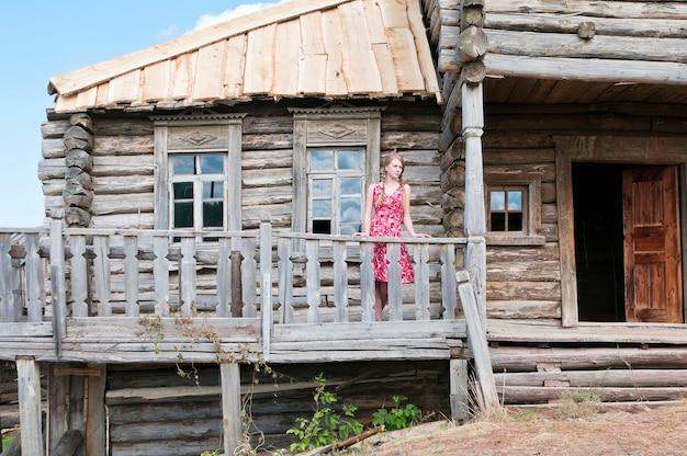 Meisje op het terras van een oud houten huis