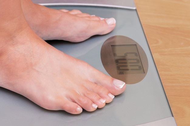Meisje op het wegen. perfect gewicht voor een meisje. weegschaal laat zien dat een meisje 50 kg weegt. gewichtscontrole. elektronische weegschalen geven het exacte gewicht weer