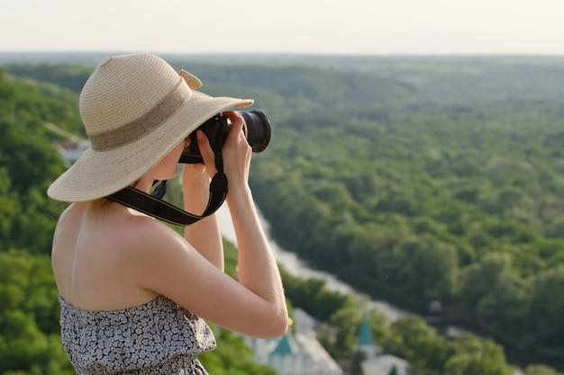 Meisje op heuvel neemt foto's tegen de achtergrond van een bos en meanderende rivier