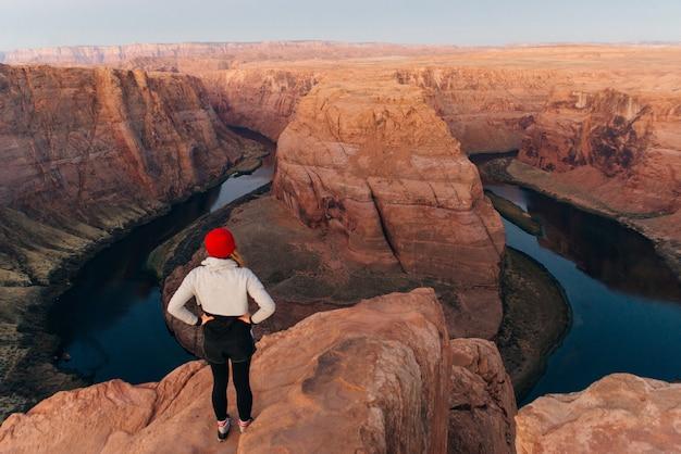 Meisje op horseshoe bend in glen canyon national recreation area in de vroege ochtend