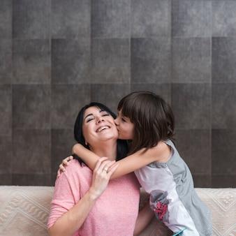Meisje op laag kussende moeder op wang