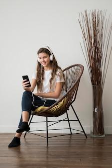 Meisje op stoel luisteren muziek op koptelefoon