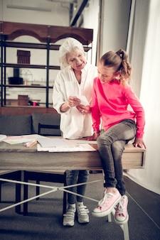 Meisje op tafel. donkerharig meisje zittend op de tafel en luisterend naar oma tijdens het spelen met flashcards