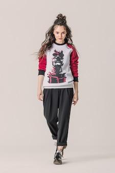 Meisje op volledige hoogte poseren in sweatshirt met daredevil-print.