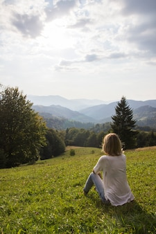 Meisje op wandeltocht genieten van de zonsondergang van bovenaf. het meisje ontspant en verfrist zich op bergachtergrond is een landschap van hoge bergen, witte wolken. meisje op de berg die de zonnige hemel bekijkt