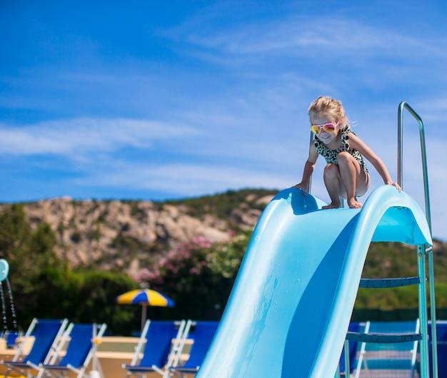 Meisje op waterglijbaan bij aquapark op de zomervakantie