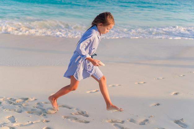 Meisje op wit strand bij zonsondergang
