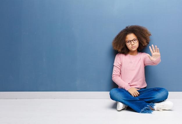 Meisje op zoek ernstig, streng, ontstemd en boos met open handpalm maken stop gebaar