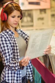 Meisje op zoek naar vinyl tijdens het luisteren naar muziek