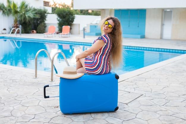 Meisje op zomervakantie tegen zwembad, gekleed gestreepte jurk en zonnebril.