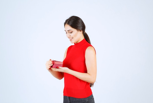 Meisje opende een rode geschenkdoos en voelt zich gelukkig.