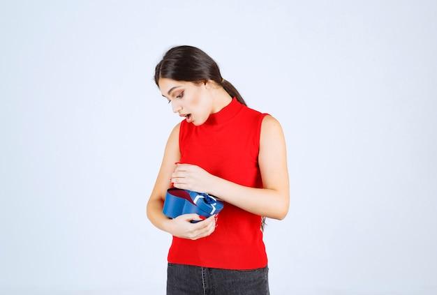 Meisje opent een blauwe geschenkdoos en wordt verrast.