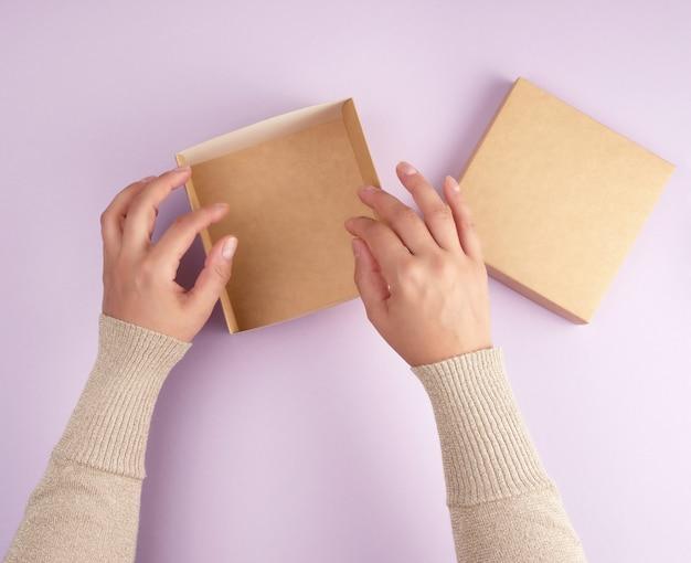 Meisje opent een bruine vierkante doos op een paarse achtergrond
