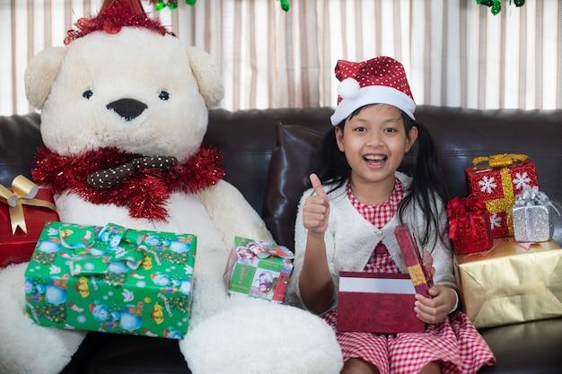 Meisje opent een geschenkdoos in eerste kerstdag