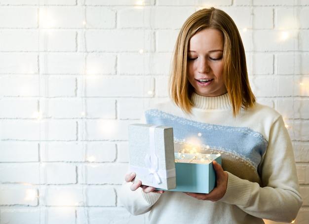 Meisje opent het geschenk en vraagt zich af. gloeiende slinger.