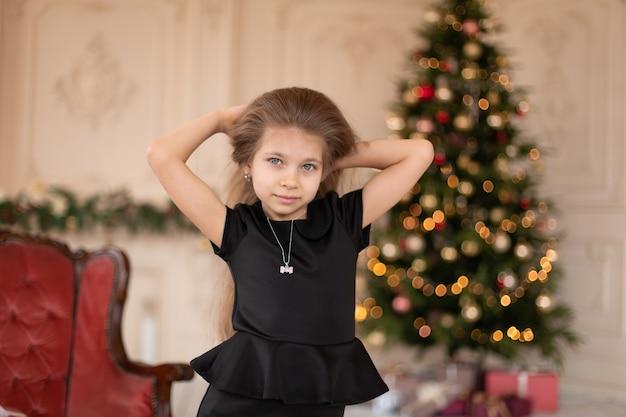 Meisje opent in de buurt van de kerstboom