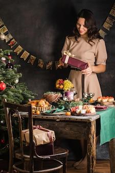Meisje opent kerstcadeau voor de tafel met kippenkoekvruchten foto van hoge kwaliteit