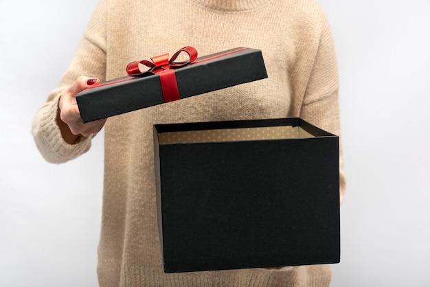 Meisje opent zwarte geschenkdoos met rode strik. viering.