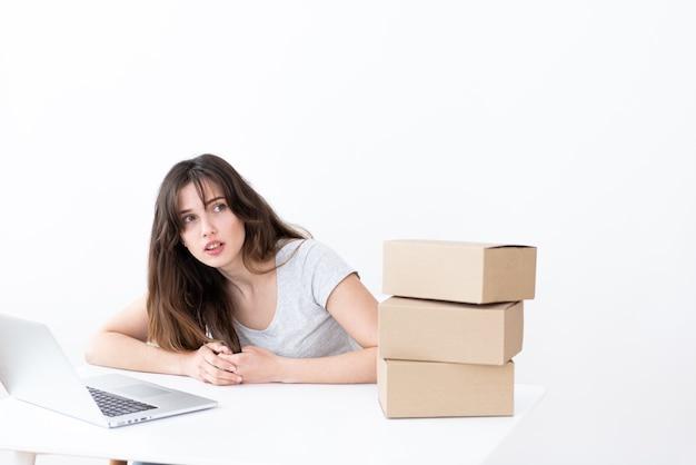 Meisje operator plaatst een bestelling voor de levering van drie dozen, specificeert details in een laptop